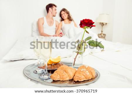 Couple in love having romantic breakfast in bedroom - stock photo