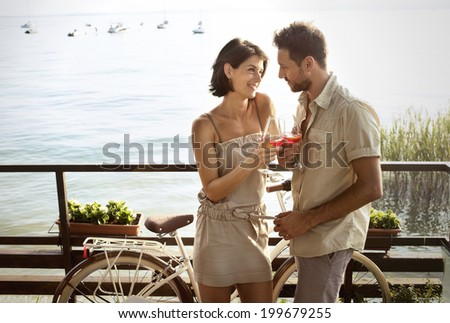 couple in love having spritz time with lake view - stock photo
