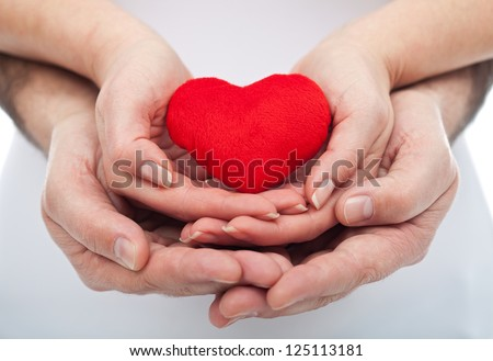 Couple in love holding a red heart in their hands - stock photo