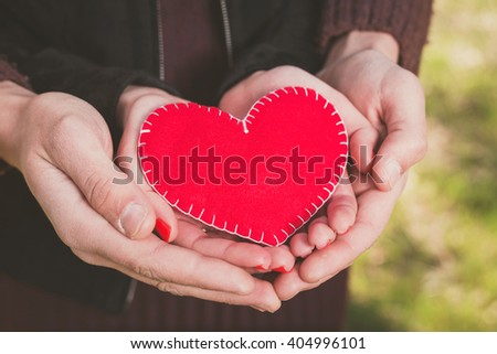 Couple in love holding a red heart in their hands outdoors