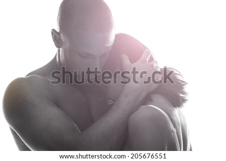 Couple in love holding each other close in a tender sentimental embrace with flare effect on a white background - stock photo