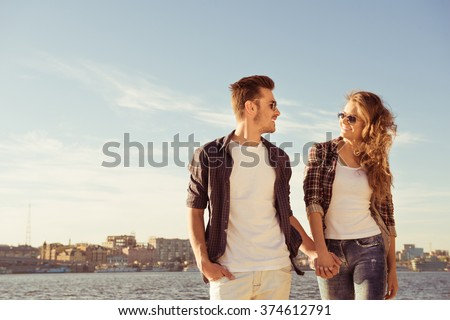 Couple in love holding hands and walking on the beach - stock photo