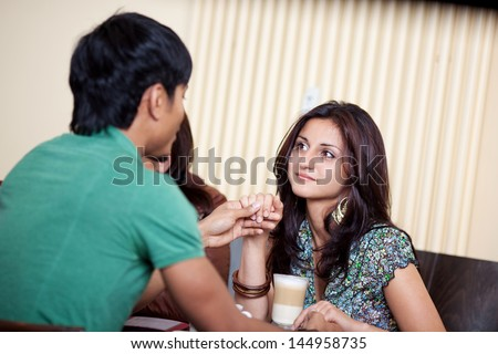 Couple in love holding hands in a cafe - stock photo