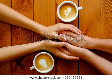 Couple in love holding hands in a cafe, top view - stock photo