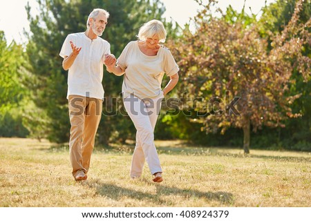 Couple in love holding hands on a walk in the park in summer - stock photo