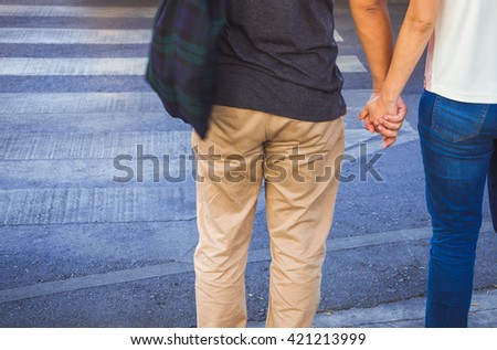 Couple in love holding hands walking cross the street