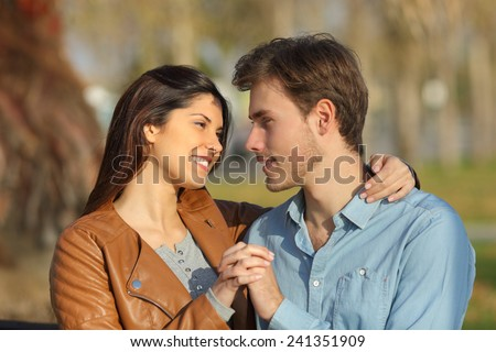 Couple in love hugging and dating sitting on a bench in a park looking each other - stock photo