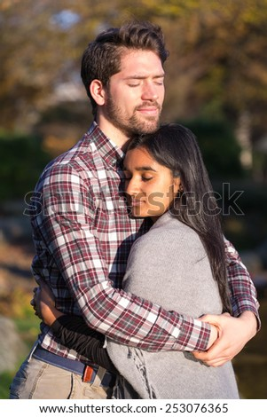 Couple in love hugging and kissing outdoors - stock photo