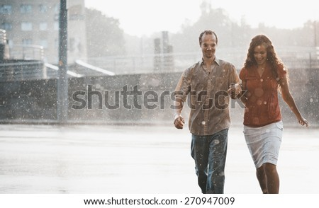 couple in love hugging and kissing under summer rain - stock photo