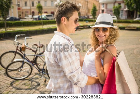 Couple in love hugging on the city square. Woman holding shopping bags and looking at camera. - stock photo