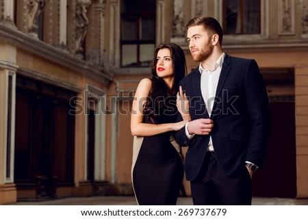 Couple in love in   elegant outfit walking in old town street . Pretty brunette woman with red lips and her handsome boyfriend have time off. - stock photo