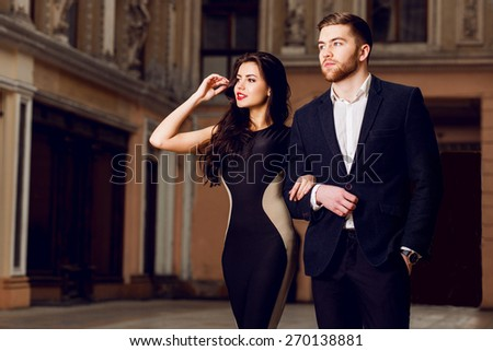 Couple in love in elegant outfit walking in old town street . Pretty brunette woman with red lips and her handsome boyfriend have time off in the evening. - stock photo