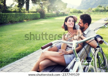 Couple in love joking together on a bench with bikes on vacation - stock photo