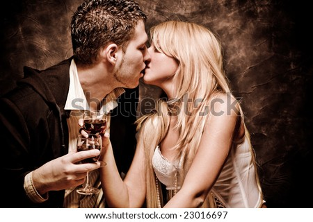couple in love, kissing and holding glasses with wine - stock photo