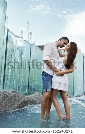 Couple in love kissing each other in fountain