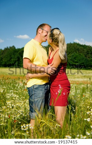 Couple in love kissing each other, standing in a field with wild flowers - stock photo