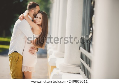 Couple in love kissing laughing having fun. Dating interracial young couple embracing on date. Pretty summer sunny outdoor portrait of young stylish couple while kissing on the street. Relationships - stock photo