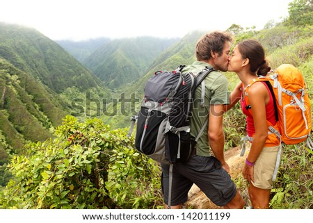 Couple in love kissing while hiking on Hawaii. Romantic young couple hikers during hike in beautiful mountain forest nature. Healthy lifestyle multi-ethnic couple on Waihee ridge trail, Maui, USA - stock photo