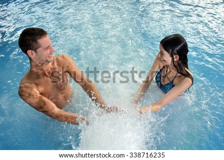 couple in love laughing and playing with a cascade of water in the pool - stock photo