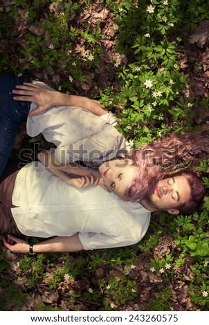 couple in love lying in the spring forest - stock photo
