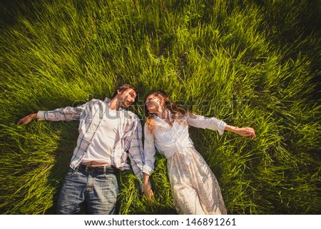 couple in love lying on green grass