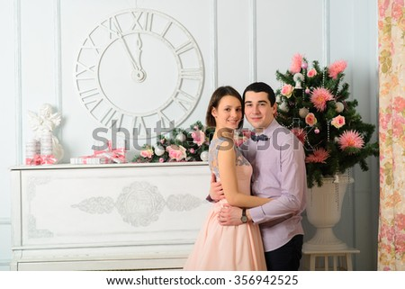 Couple in love near the piano. New Year, Christmas, holiday. Romantic evening - stock photo