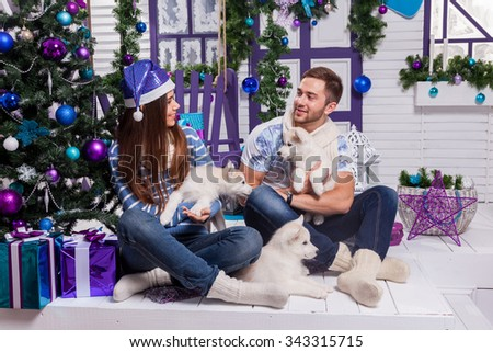 couple in love on a white terrace sits on the swing next to a Christmas tree and presents, playing with puppies Husky and Eskimo dog.