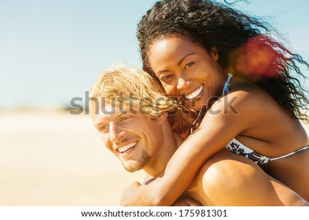 Couple in love on beach - Caucasian man having his Hispanic woman piggyback on his back under blue sky near ocean - stock photo