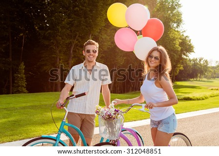 couple in love on bikes with balloons and flowers - stock photo
