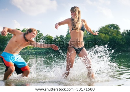 Couple in love on the beach of a lake - he is chasing her trying to splash some water on her in a playful way - stock photo