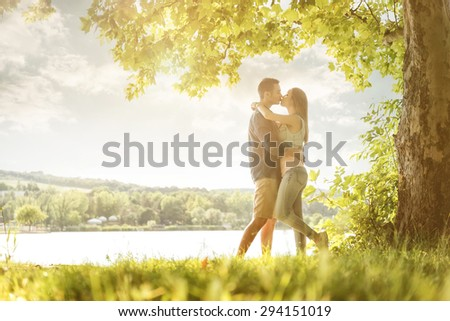 Couple in love on the lake, beneath the trees, kissing - stock photo