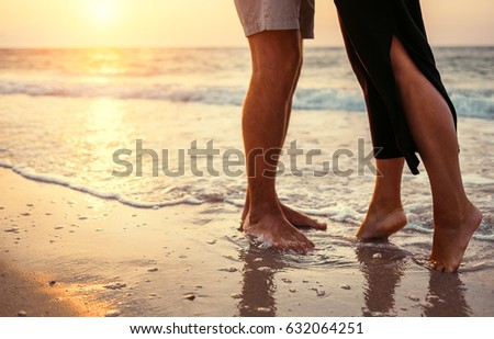 Couple in love on the sunrise sea side. Close up legs image
