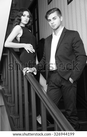 Couple in love on wooden stairs - stock photo