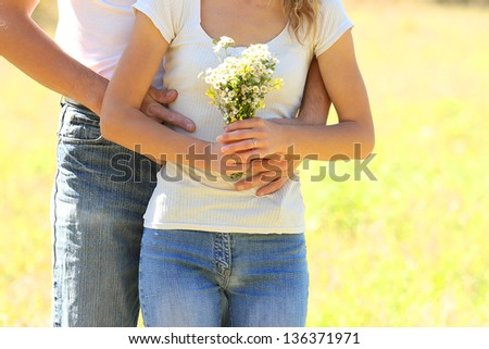couple in love outdoors with a bouquet of flowers - stock photo