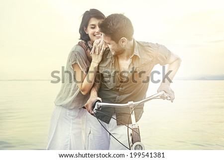 couple in love pushing bicycle together - stock photo