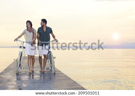couple in love pushing bike on a boardwalk at the lake at sunset - stock photo