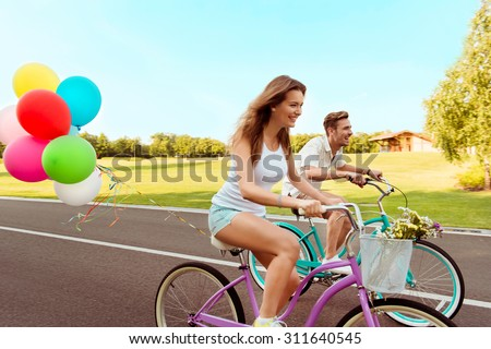 couple in love  riding a bicycle race with balloons - stock photo
