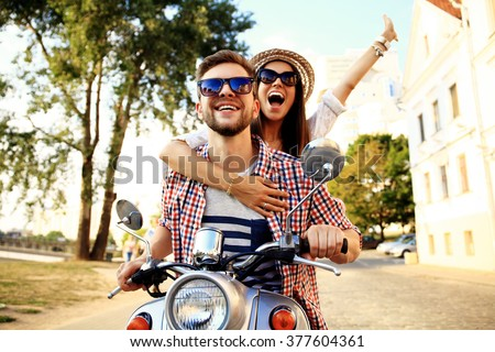 Couple in love riding a motorbike , Handsome guy and young sexy woman travel . Young riders  enjoying themselves on trip. Adventure and vacations concept.