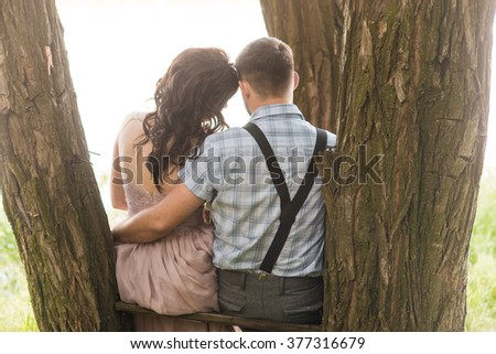 Couple in love sits on the tree back view. Noise and toned image - stock photo