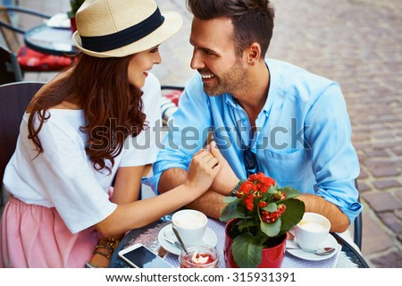 Couple in love sitting in cafe looking at each other - stock photo
