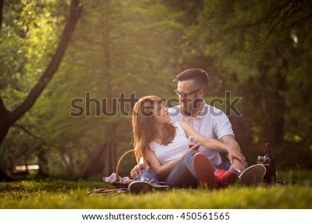 Couple in love sitting on a picnic blanket in a park, talking to each other, drinking wine and enjoying a beautiful, peaceful day in nature - stock photo
