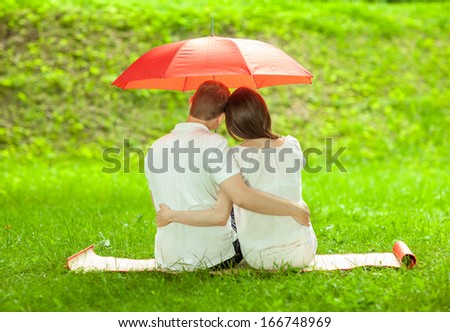 Couple in love sitting on green summer meadow under red umbrella embracing each other - stock photo