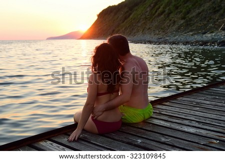 Couple in love sitting on the edge of the pier and hugs - stock photo