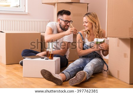 Couple in love sitting on the floor in their new apartment surrounded by cardboard boxes, eating take out chinese food and drinking ice tea - stock photo