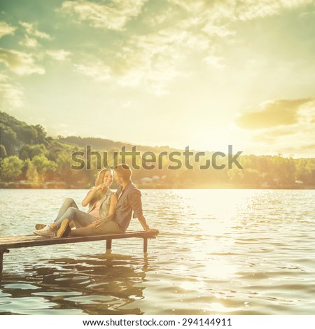 Couple in love sitting on the pier - stock photo