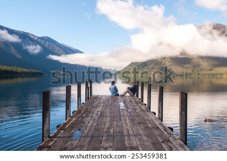 couple in love sitting on the pier at Nelson Lake National Park in the South Island of New Zealand - stock photo
