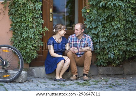 Couple in love sitting on the steps at the door of the house. Man and woman during honeymoon. - stock photo