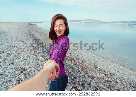Couple in love. Smiling beautiful young woman holding man's hand and leading him on beach near the sea. Point of view shot - stock photo
