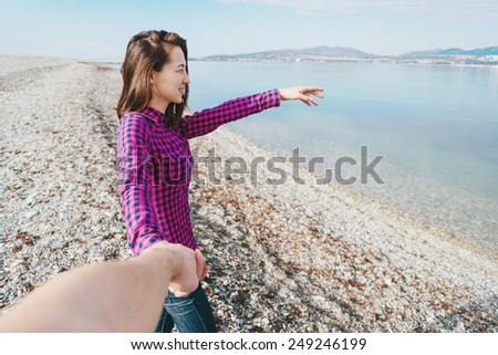 Couple in love. Smiling beautiful young woman holding man's hand and showing him something in distance on beach near the sea. Point of view shot - stock photo