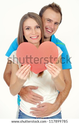 Couple in love smiling holding a red heart - stock photo